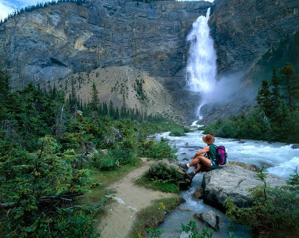 Vilande vandrare vid vattenfall.