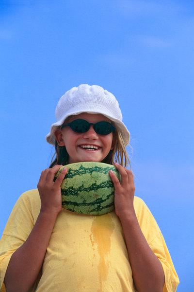 Flicka äter melon.