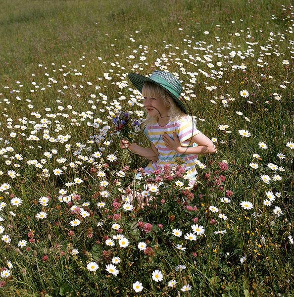 Flicka på blomsteräng