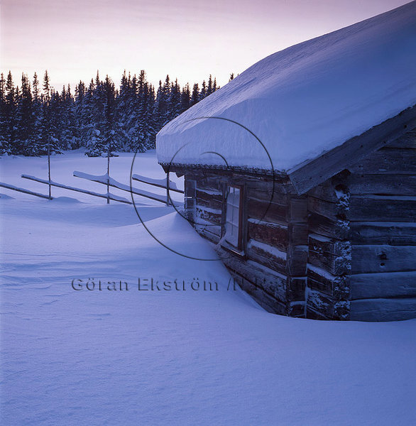 Fäbodstuga i vinterskymning