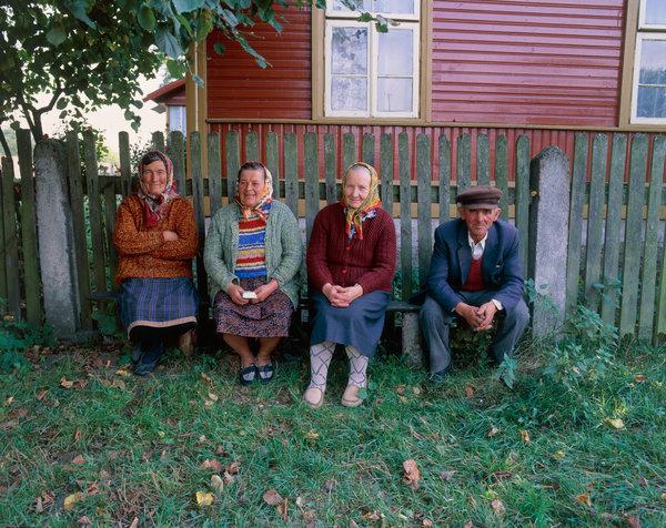 Tre gummor och en gubbe sitter på en bänk.