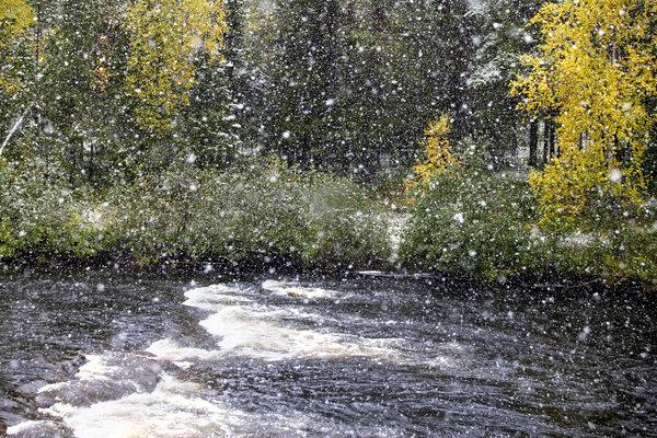 Snöfall vid ån.
