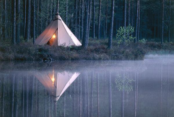 Ljus i kåta vid skogstjärn.