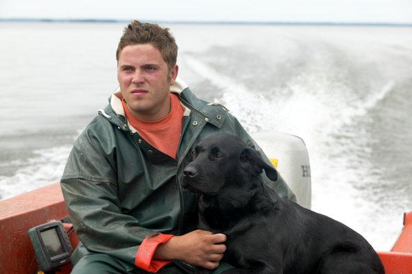Ung yrkesfiskare med sin hund.
