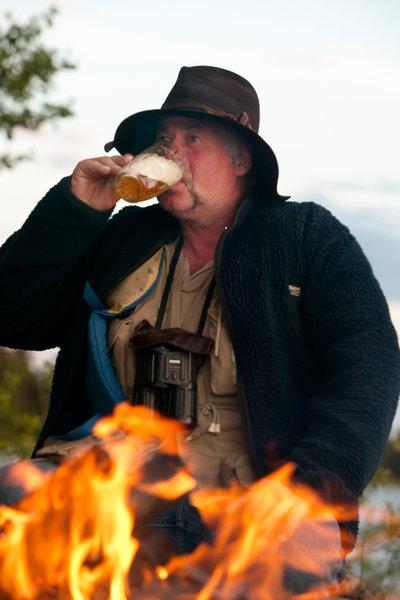 Människa vid lägereld dricker öl.